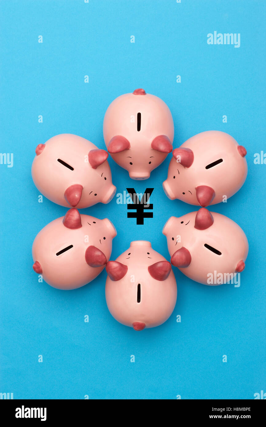 Piggy banks surrounding a Yen Yuan symbol view from above - Stock Image