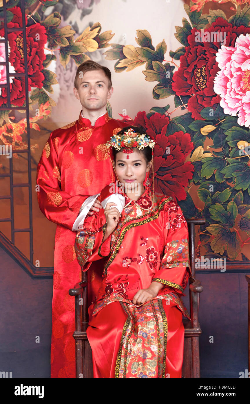 23c2422f88849 Mixed Race Bride and Groom in Studio wearing traditional Chinese wedding  outfits - Stock Image