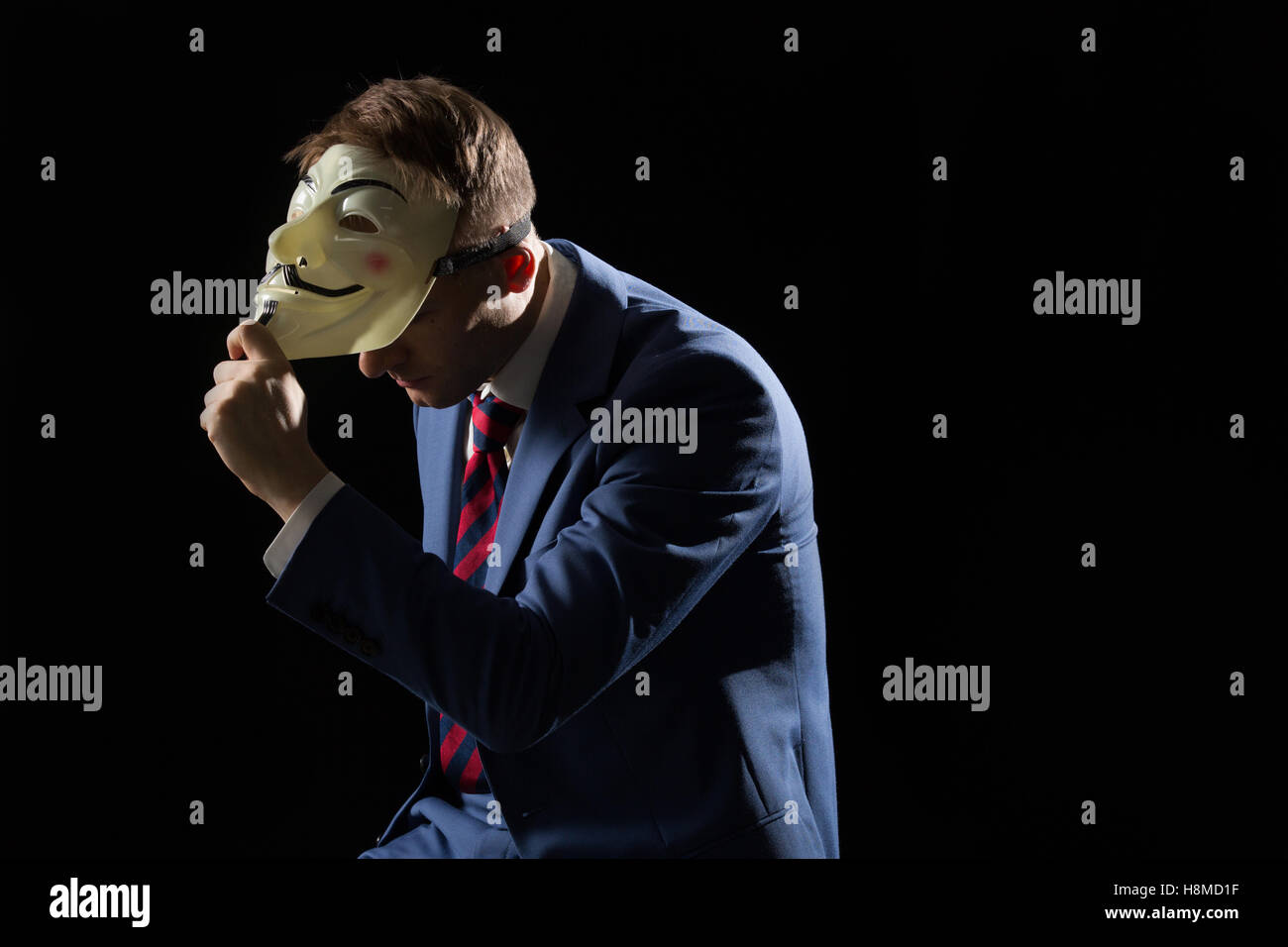 Business man under the mask disguise being  Anonymous and implying that he is a hacker or anarchist - Stock Image