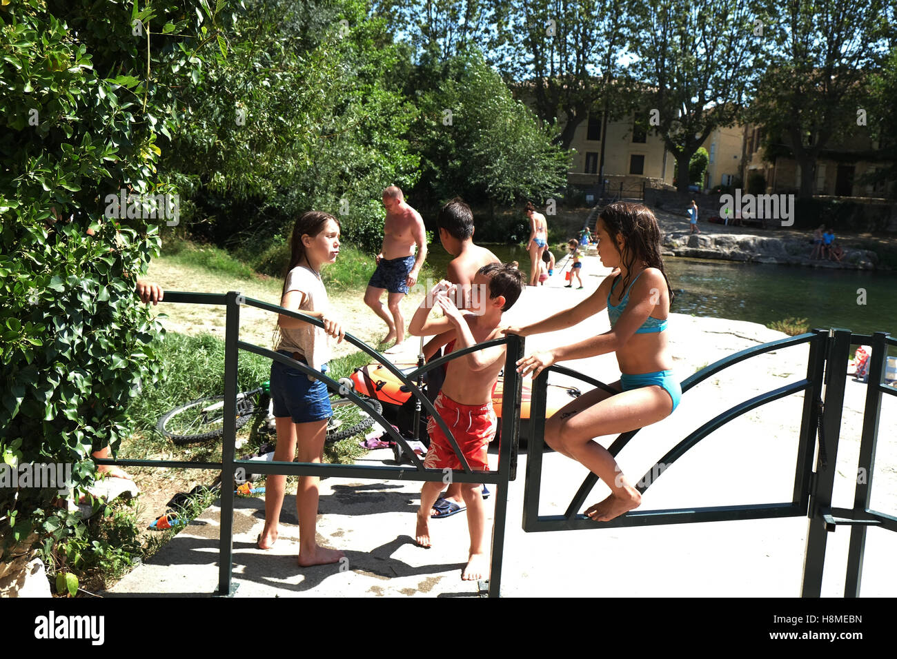 young friends play ion the summer sunshine meeting in the middle of the village by the water - Stock Image