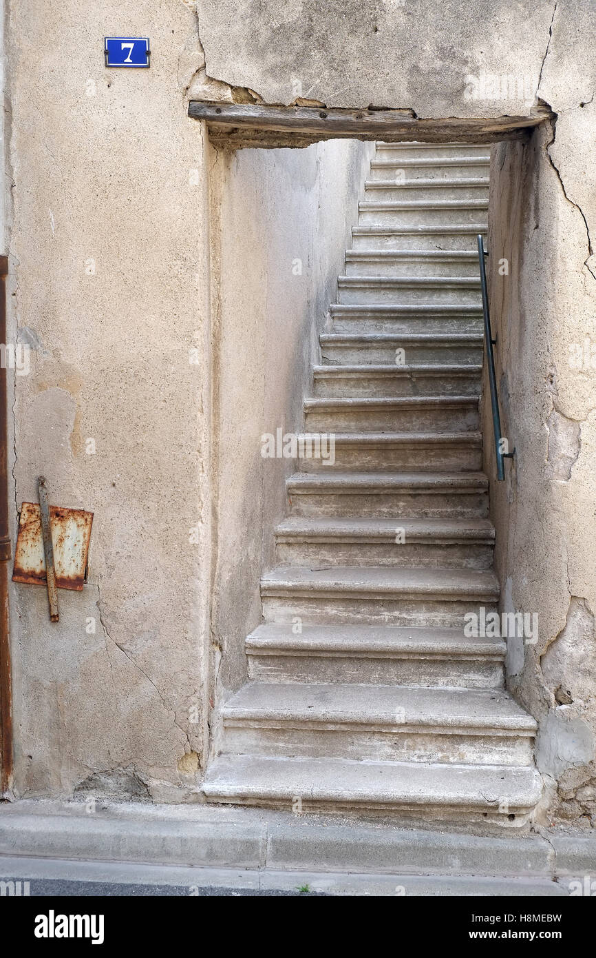 external stone stair case rising into an unseen property in the French town of Olonzac - Stock Image