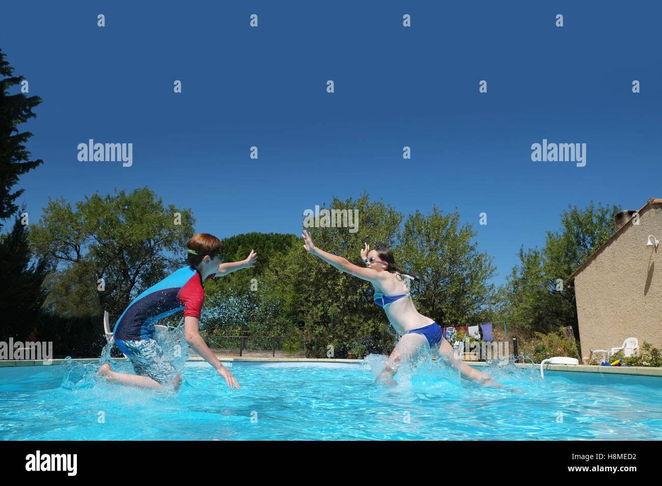 two children play in a swimming pool jumping and trying to meet in the middle and high five each others hands in - Stock Image