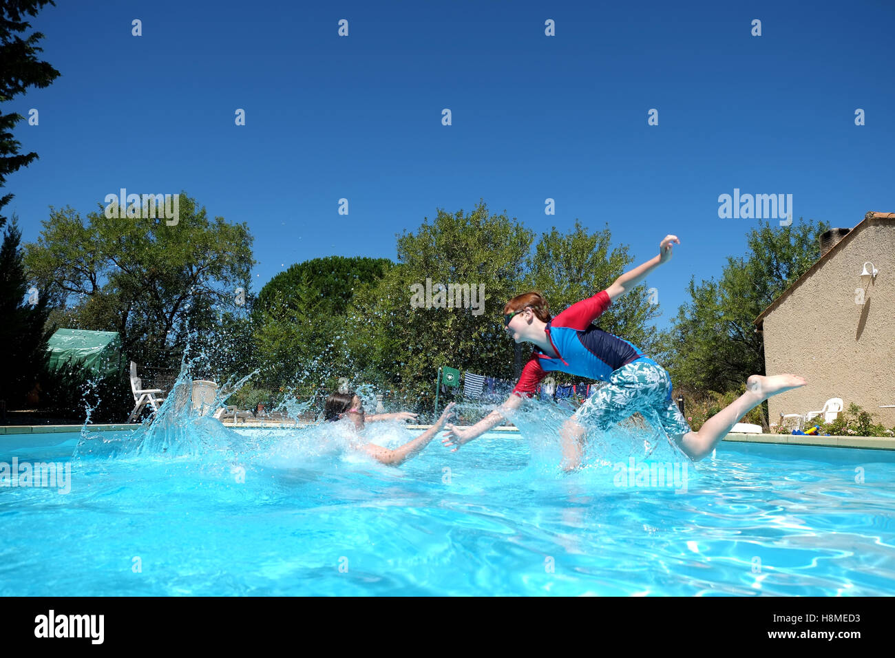 two children play in a swimming pool jumping and trying to meet in the middle and high five each others hands - Stock Image
