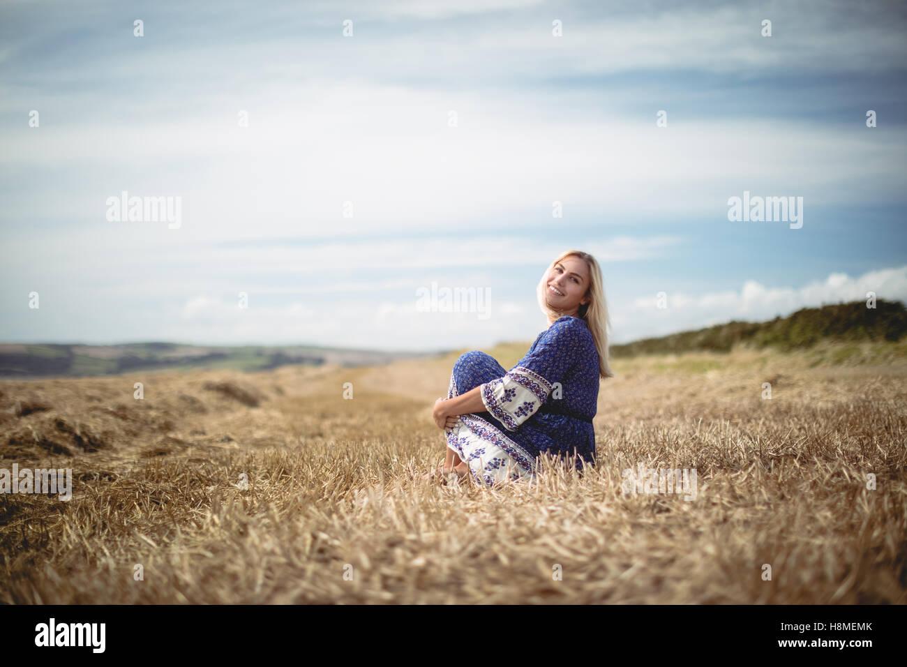 Blonde woman sitting in field - Stock Image