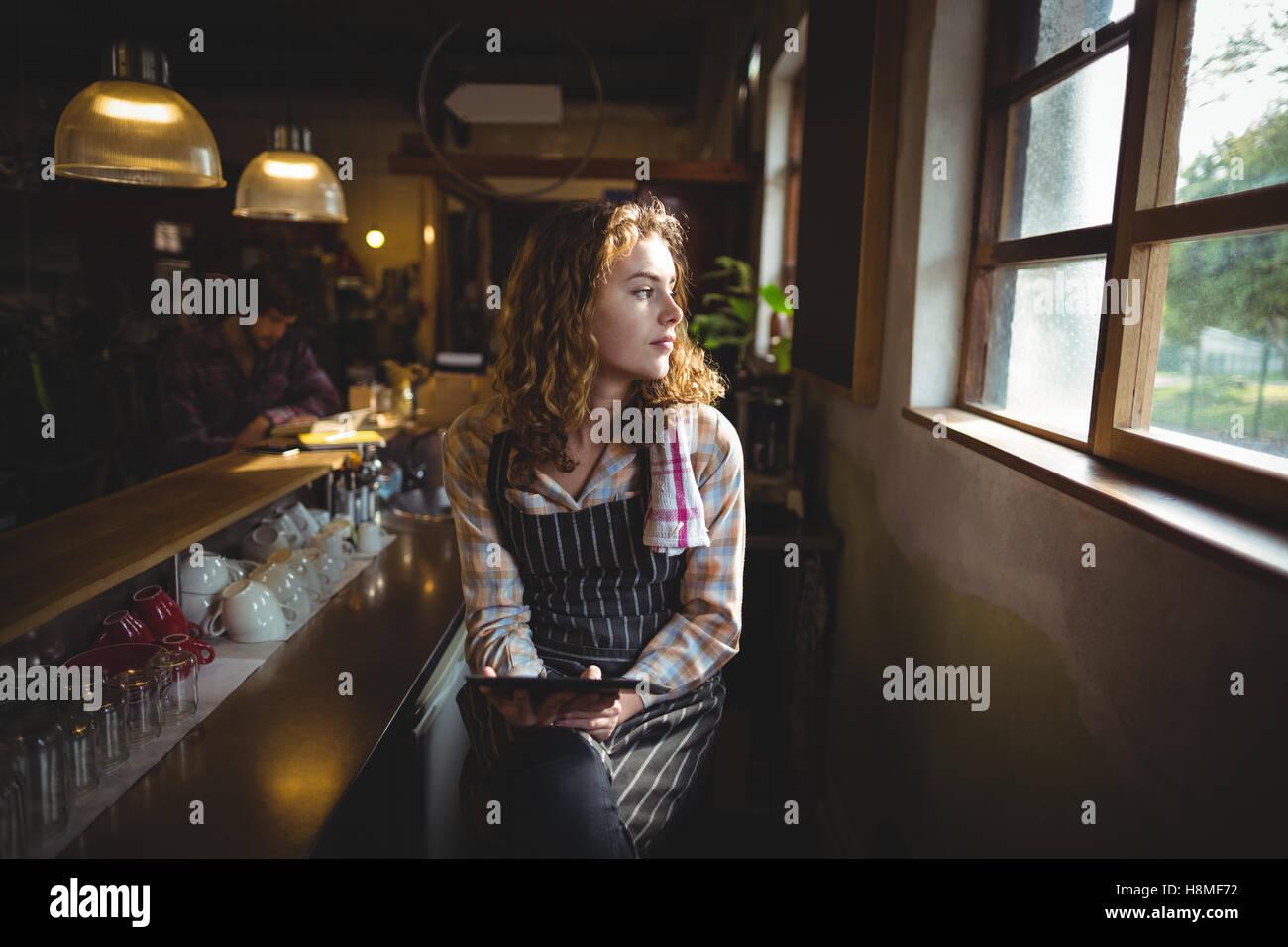 Thoughtful waitress looking through window - Stock Image