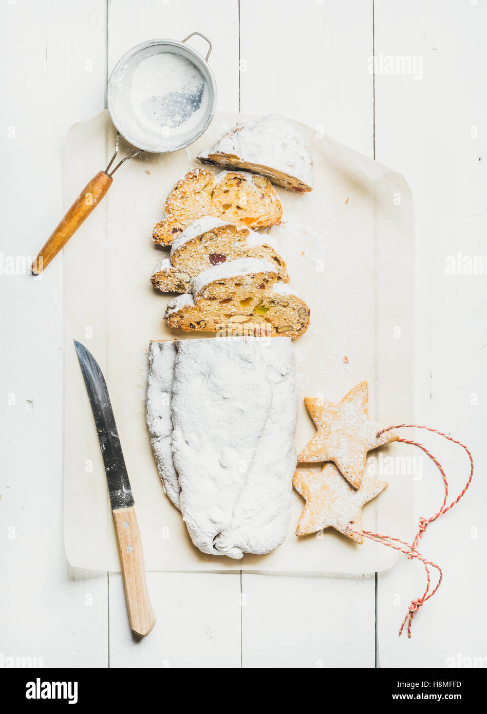 Traditional German Christmas cake Stollen cut in pieces, cookies, sieve - Stock Image