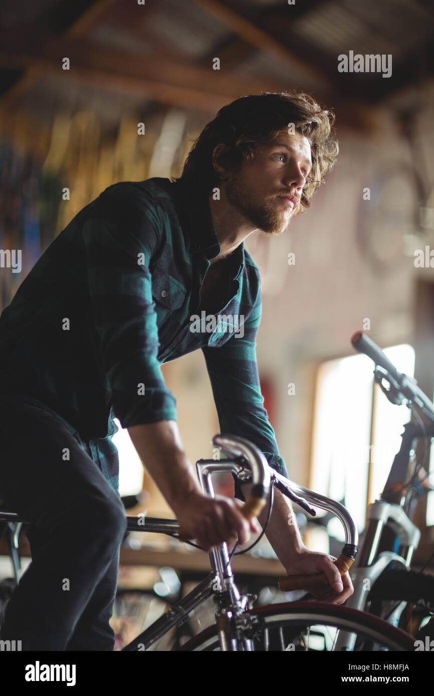 Mechanic trying bicycle - Stock Image