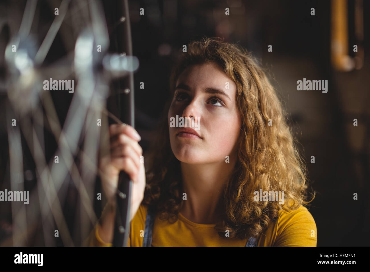 Mechanic examining a bicycle wheel - Stock Image