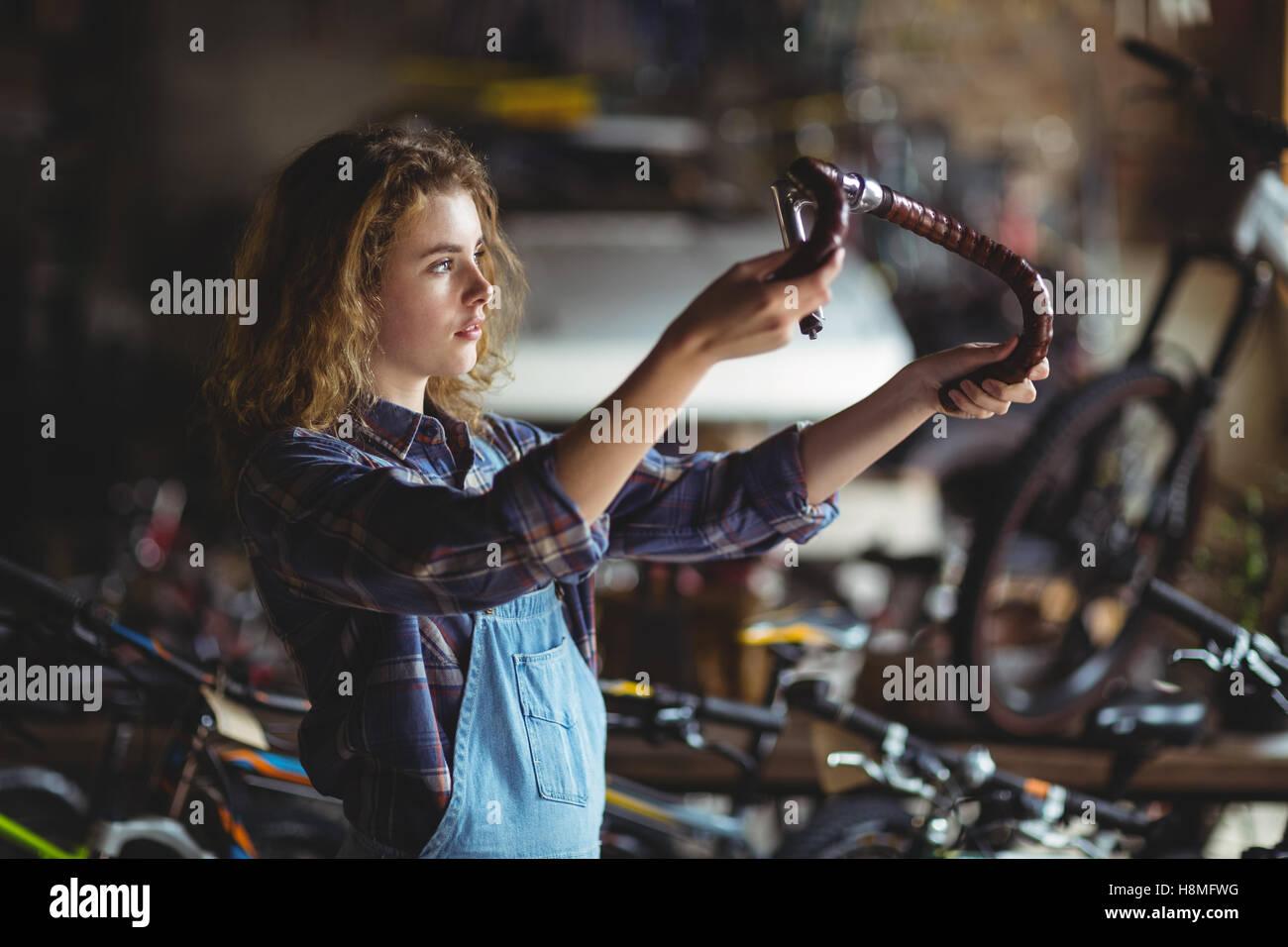 Mechanic examining a bicycle handle bar - Stock Image