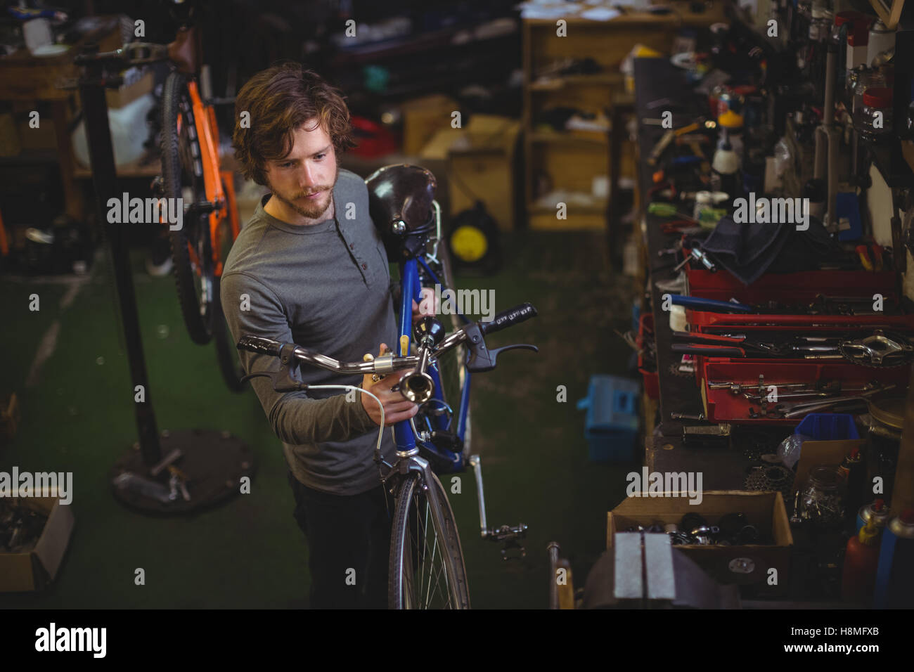 Mechanic carrying a bicycle - Stock Image
