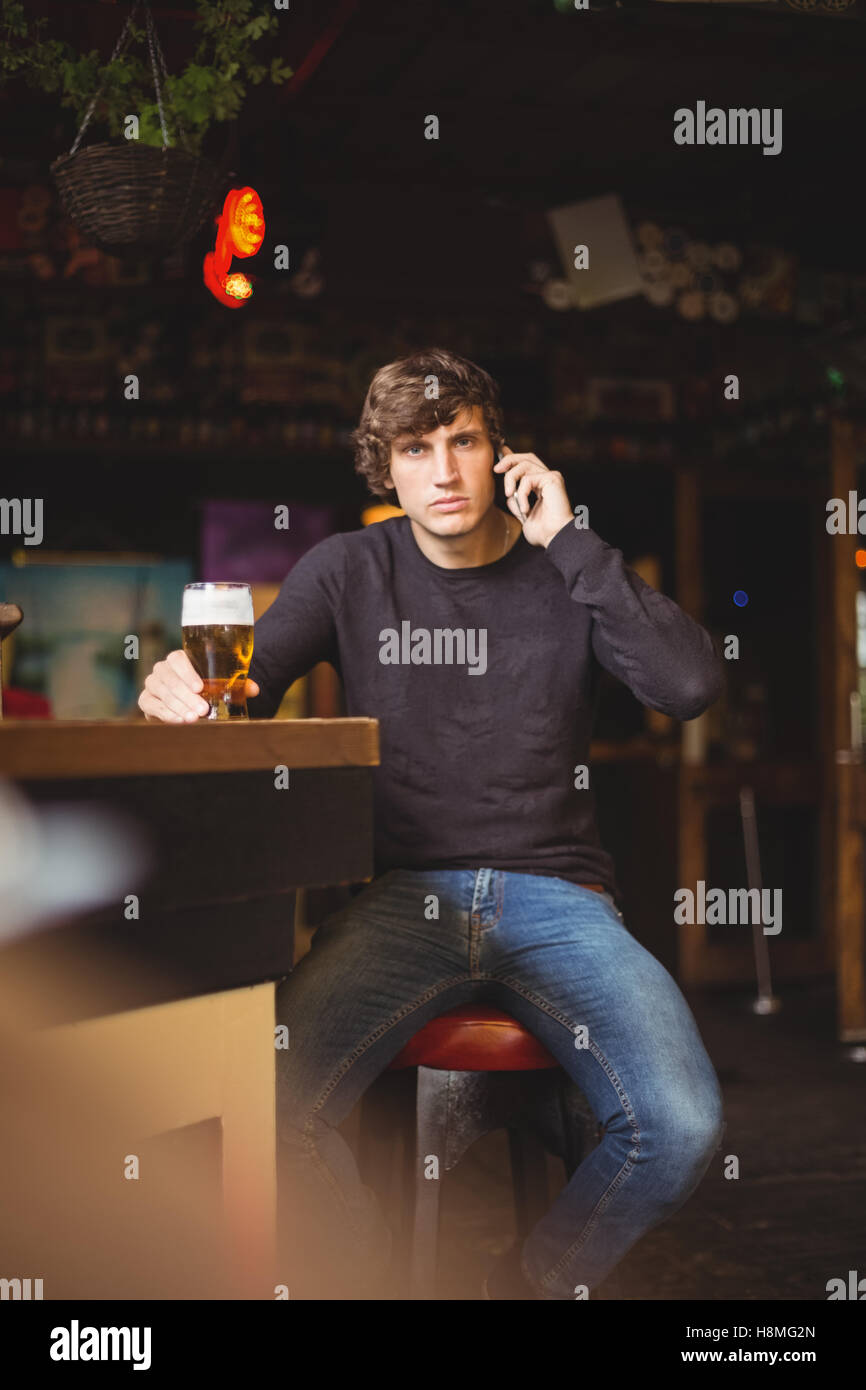 Man talking on mobile phone in bar - Stock Image