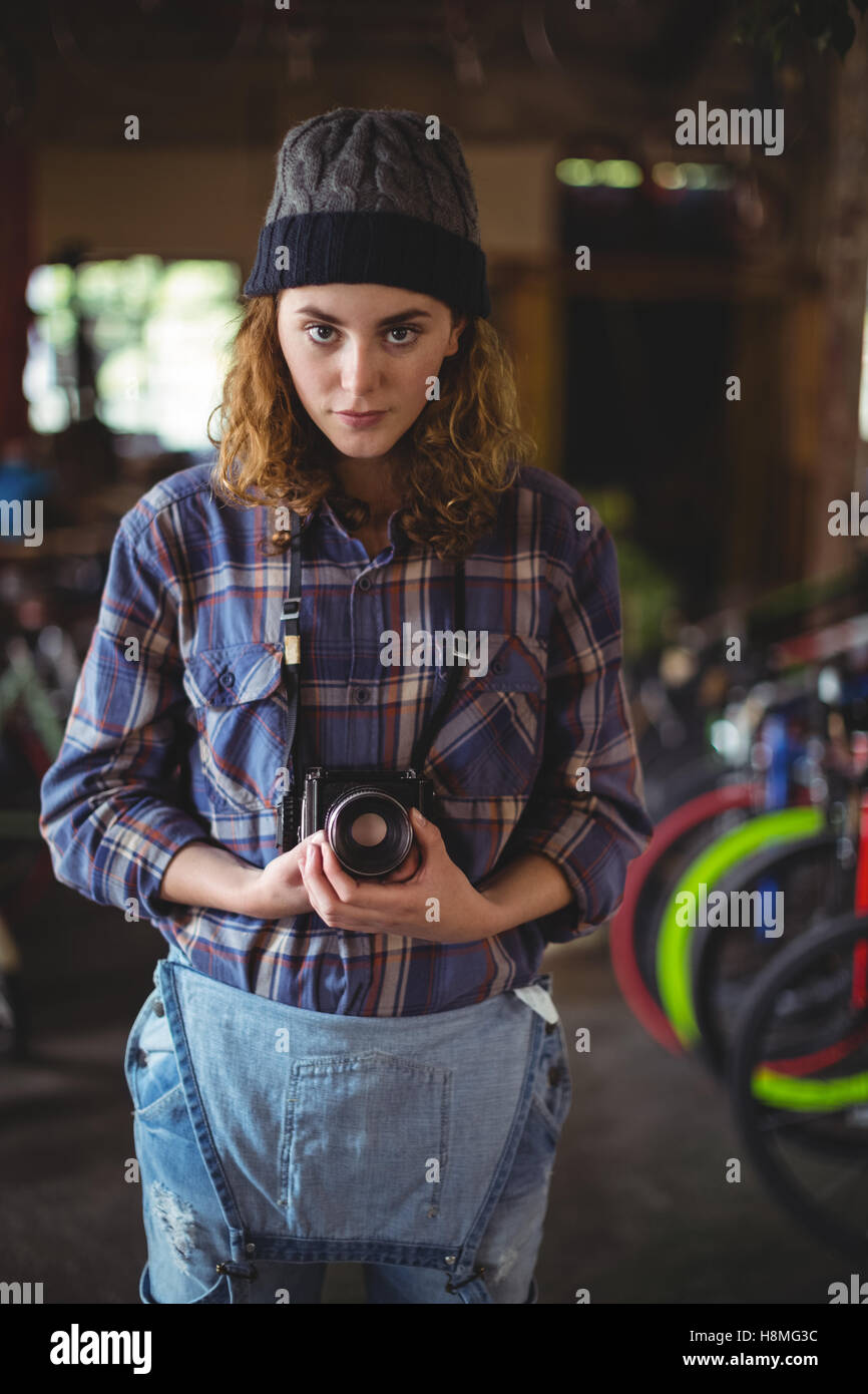 Woman adjusting vintage camera in bicycle shop Stock Photo