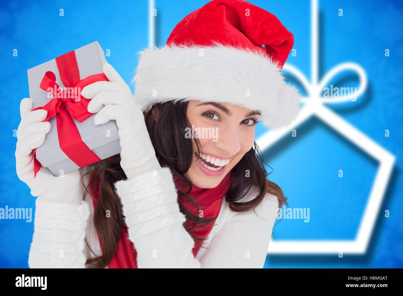 bf72d8cab1ff8 Excited woman in santa hat holding her christmas gift Stock Photo ...