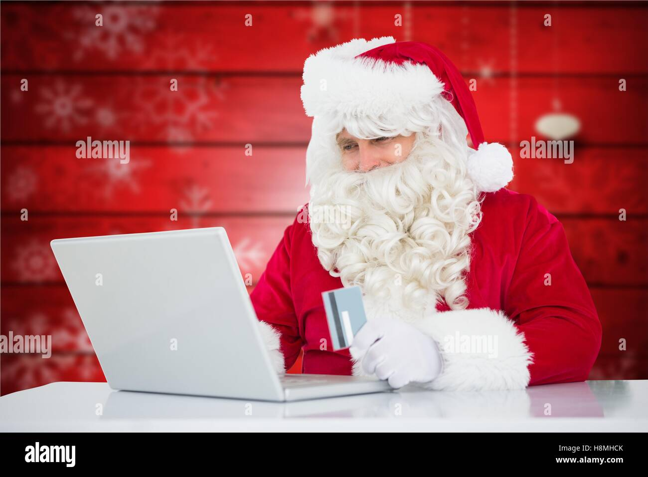 Santa claus doing online shopping with credit card on laptop Stock Photo