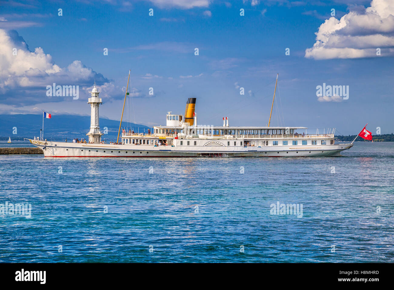 Traditional paddle steamer excursion ship with historic Les Paquis Lighthouse on famous Lake Geneva, Geneva, Switzerland - Stock Image