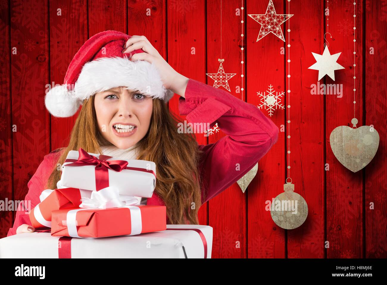 Confused woman in santa costume with a stack of christmas gifts - Stock Image