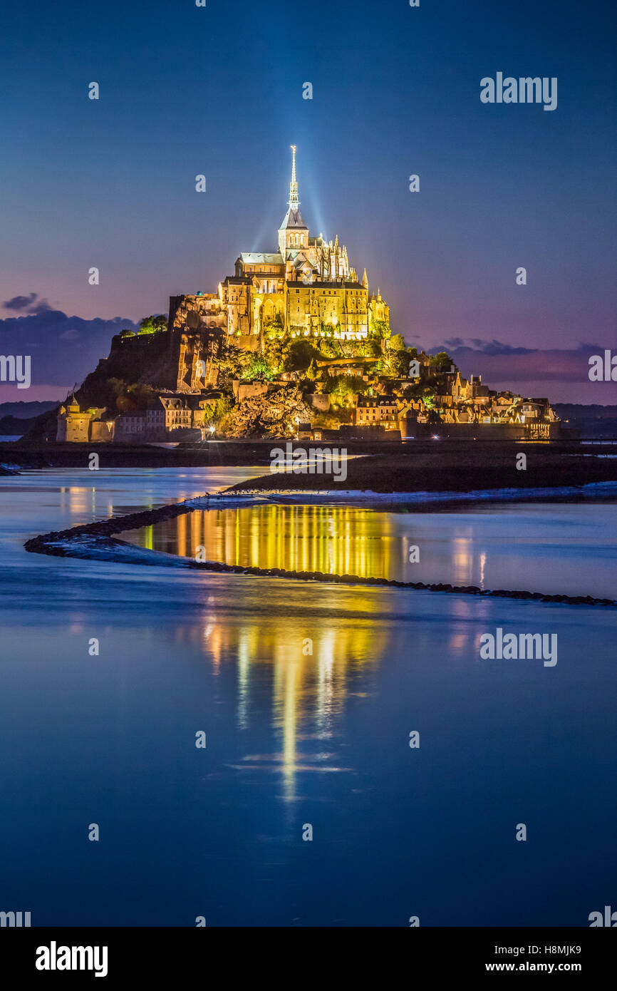 Classic view of famous Le Mont Saint-Michel tidal island in beautiful twilight during blue hour at dusk, Normandy, - Stock Image