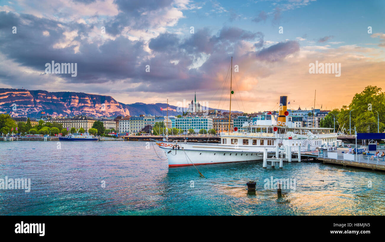 Classic view of the historic city center of Geneva with traditional paddle steamer boat on Lake Geneva at sunset, - Stock Image