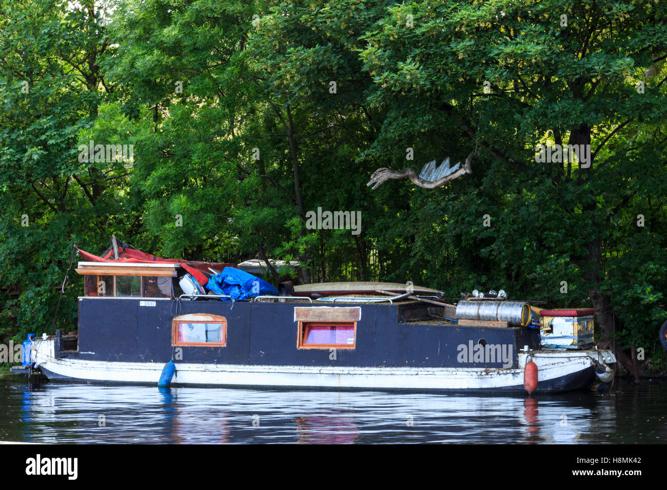 A wooden dragon sculpted from driftwood above a narrowboat on the River Lea, Upper Clapton, London, UK - Stock Image