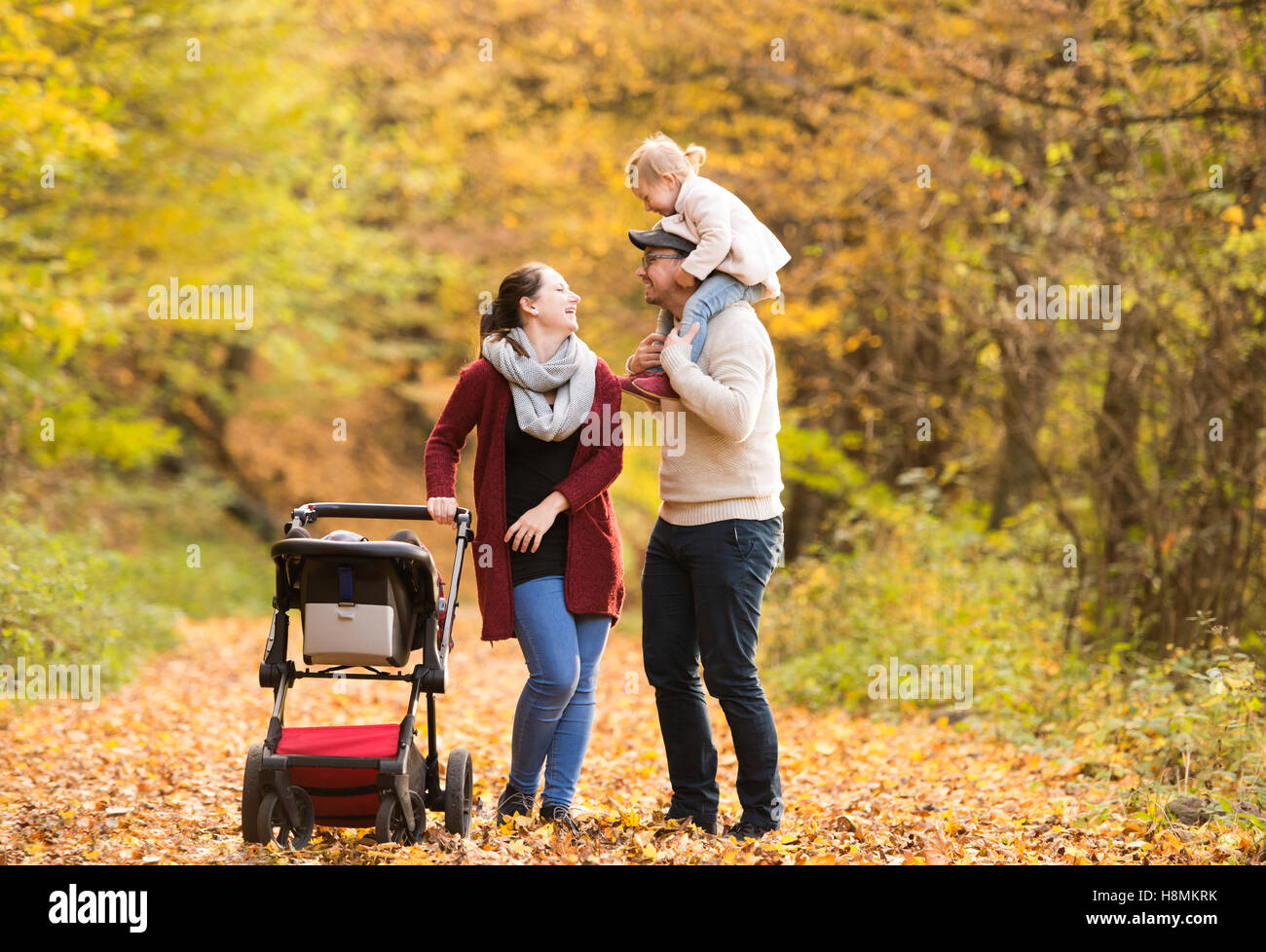 Beautiful young family on a walk in autumn forest. - Stock Image