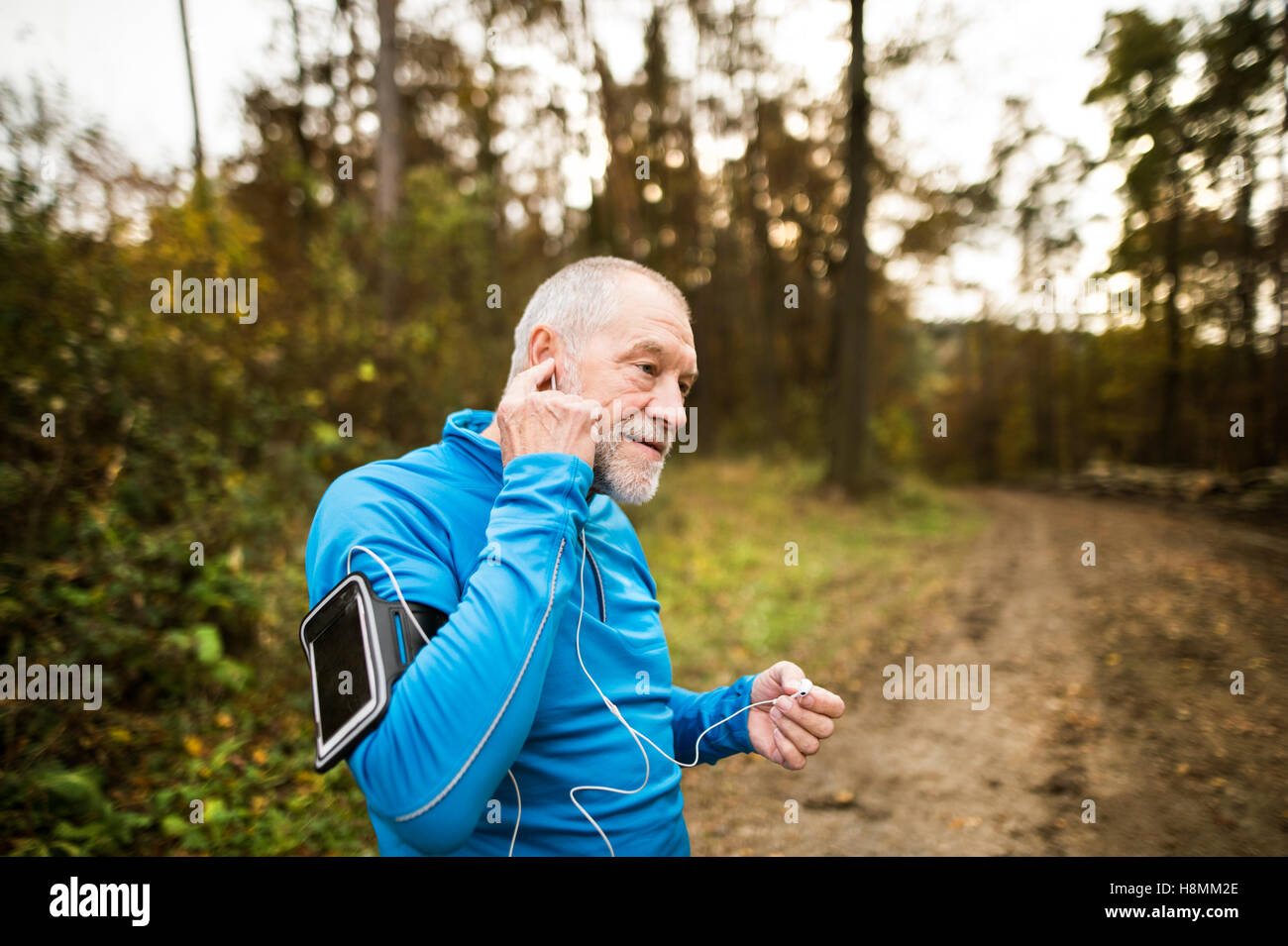 Senior runner in nature with smart phone and earphones. - Stock Image