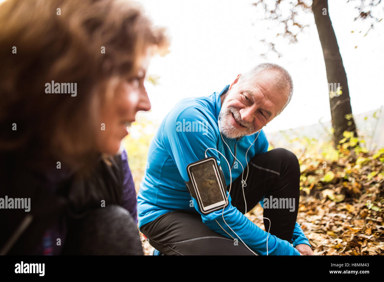 Senior runners in nature, tying shoelaces. Man with smartphone. Stock Photo