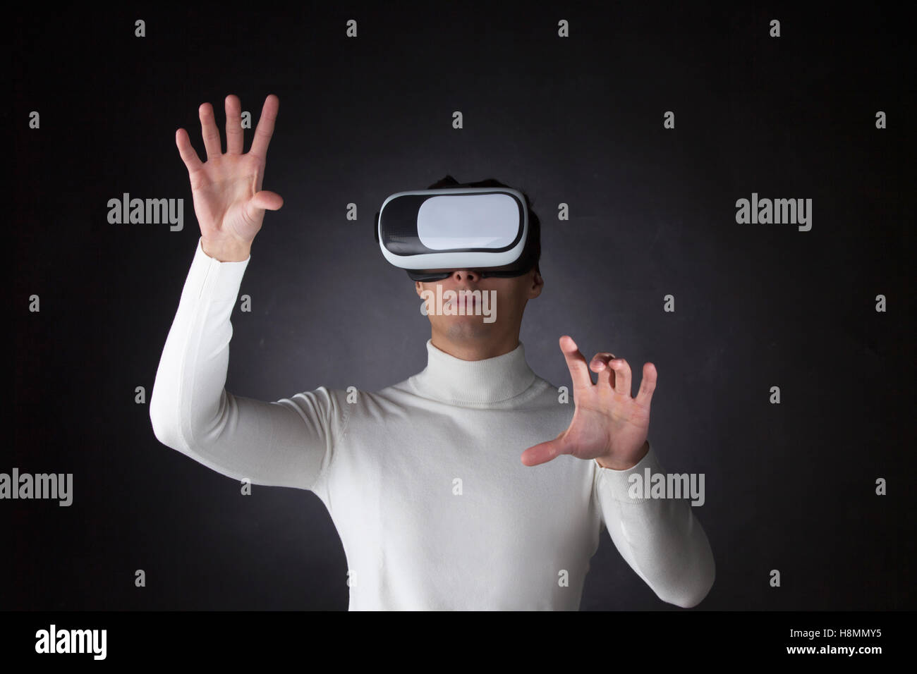 Man wearing virtual reality goggles and pointing fingers to empty space - Stock Image