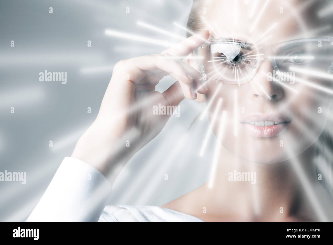 Woman in virtual reality glasses and hologram rays - Stock Image