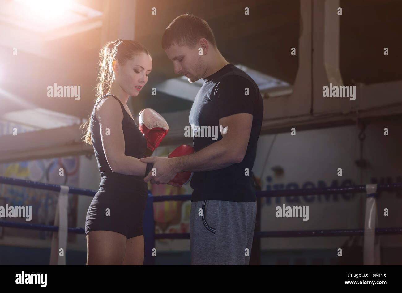 The coach puts on the boxing gloves young athlete before the fight. Backlight. - Stock Image
