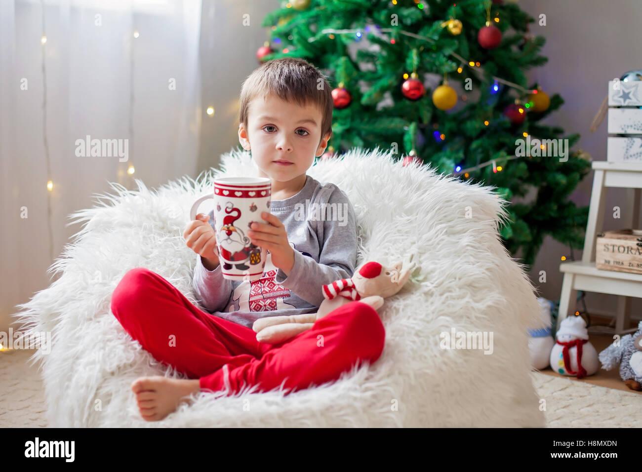 Cute boy, sitting on bean bag, drinking tea and enjoying Christmas holidays, Christmas decoration around him - Stock Image