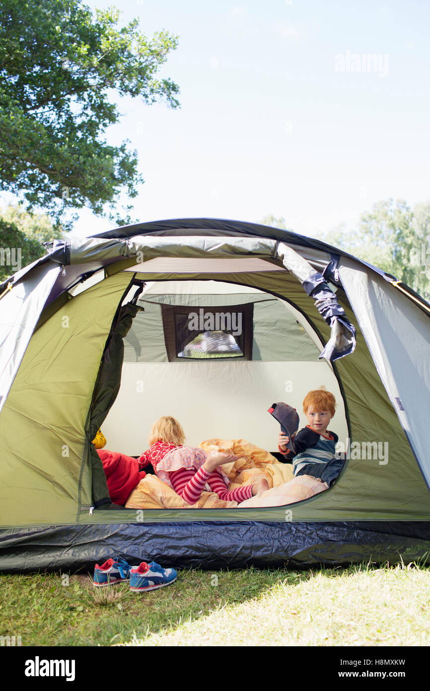 Brother (4-5) and sister (6-7) in tent - Stock Image