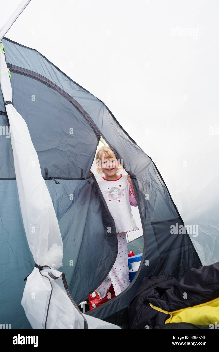 Smiling girl (4-5) in pajamas standing in grey tent - Stock Image