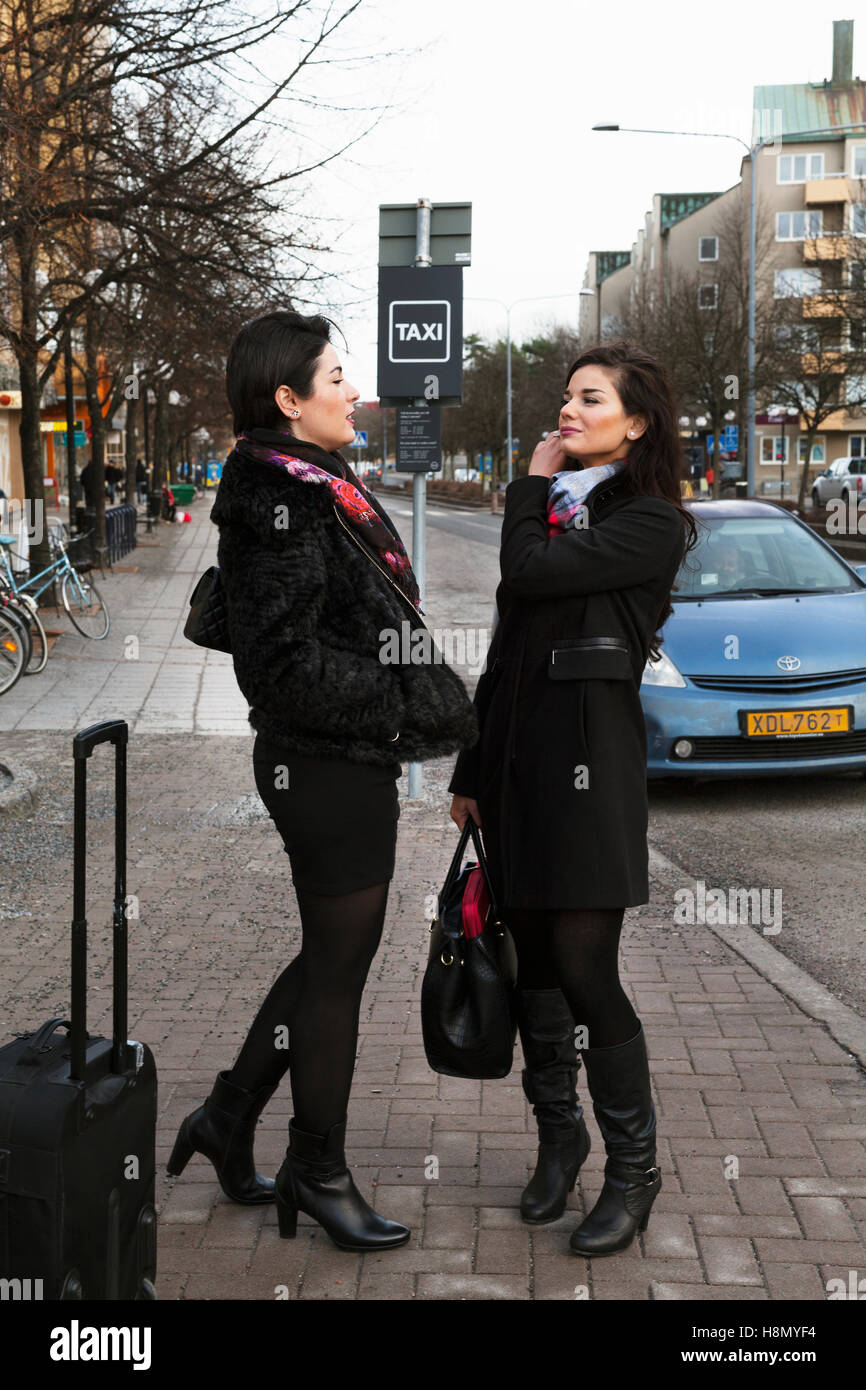 Women talking on pavement - Stock Image