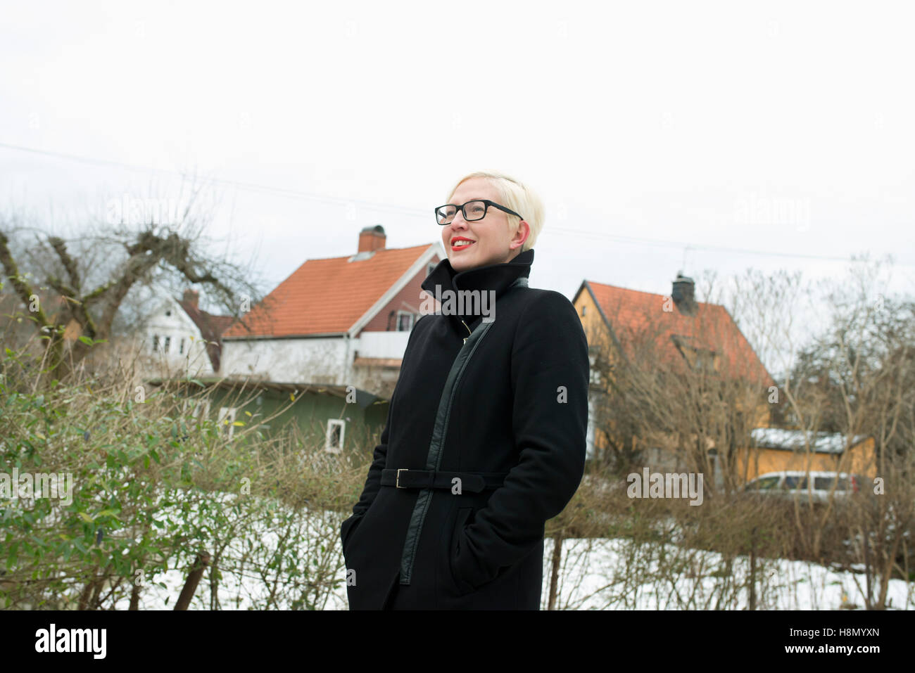 Blonde woman wearing overcoat standing against houses Stock Photo