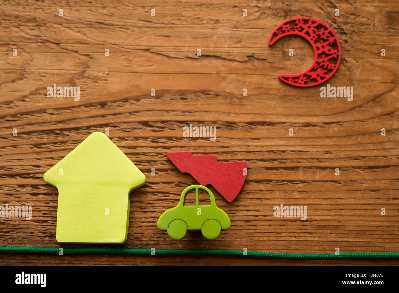 Christmas card. Merry Christmas and Happy New Year. Christmas tree move on green car near house under red moon. - Stock Image