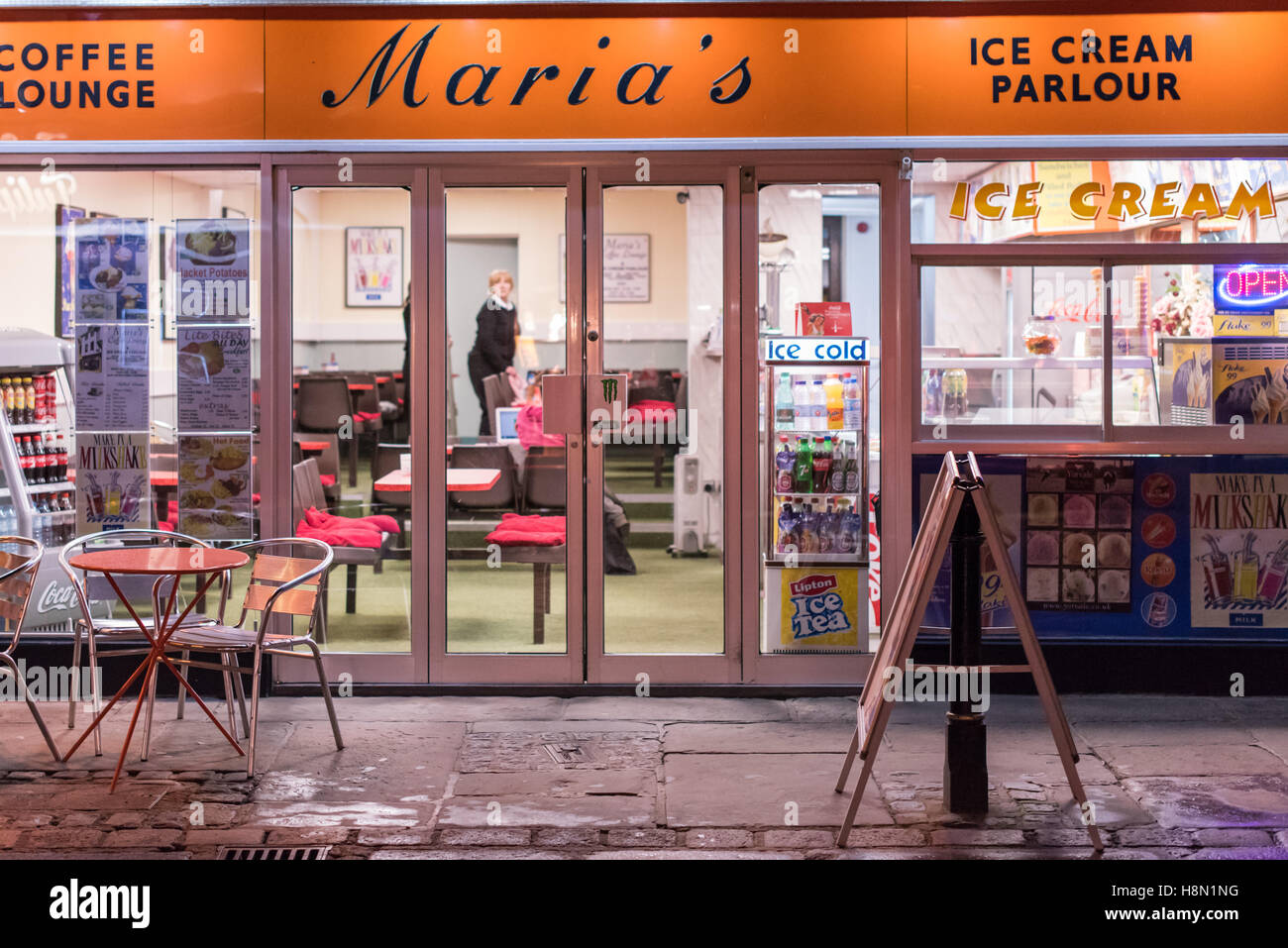 Looking through the window of a cafe at night on Canterbury High Street. A mature woman can be seen inside the ice - Stock Image