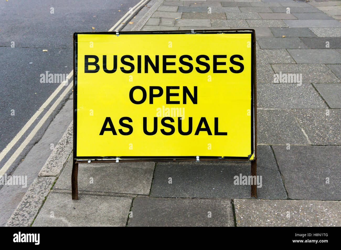 A yellow Businesses Open as Usual sign. - Stock Image