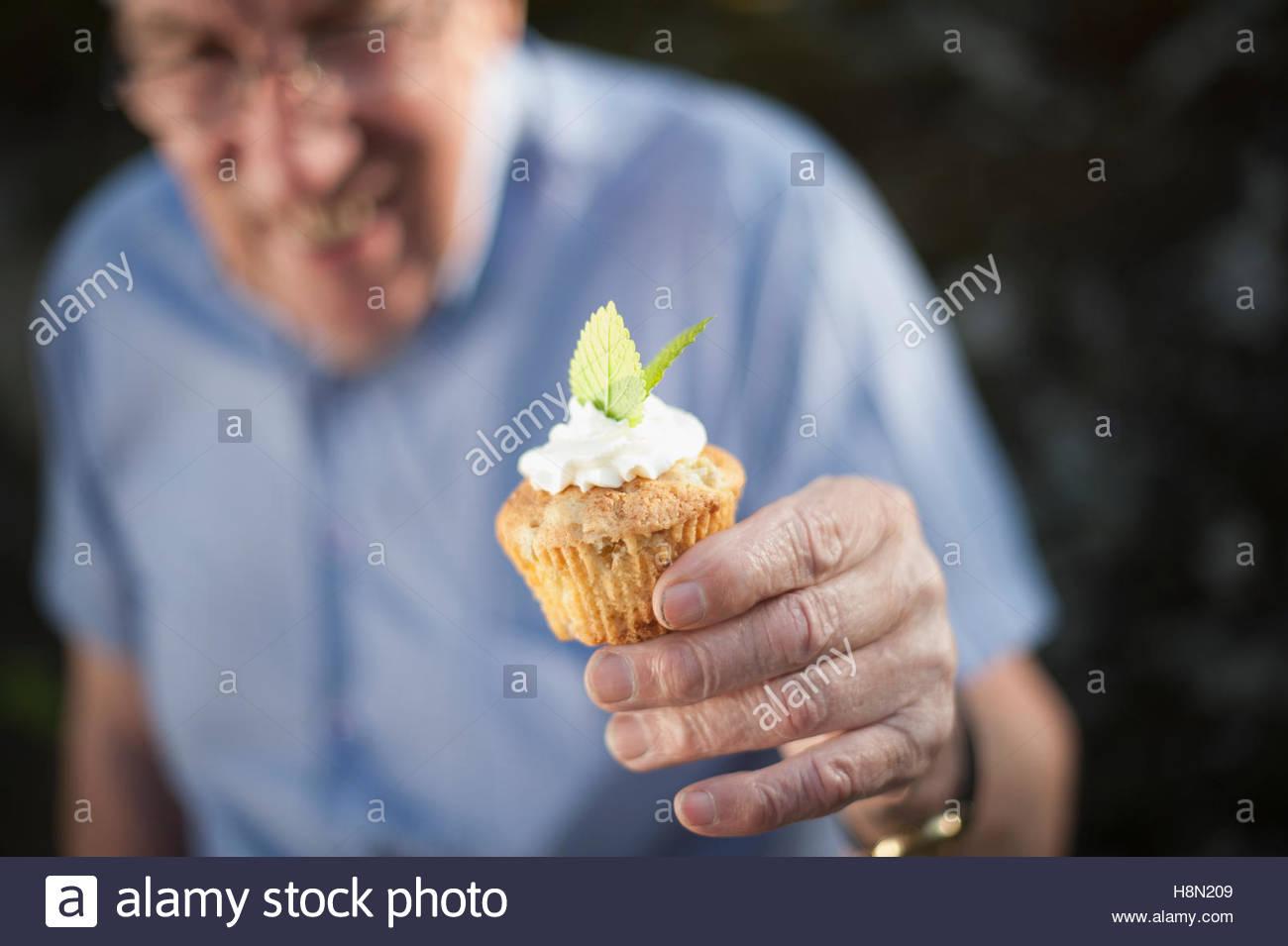 Senior man holding cupcake - Stock Image