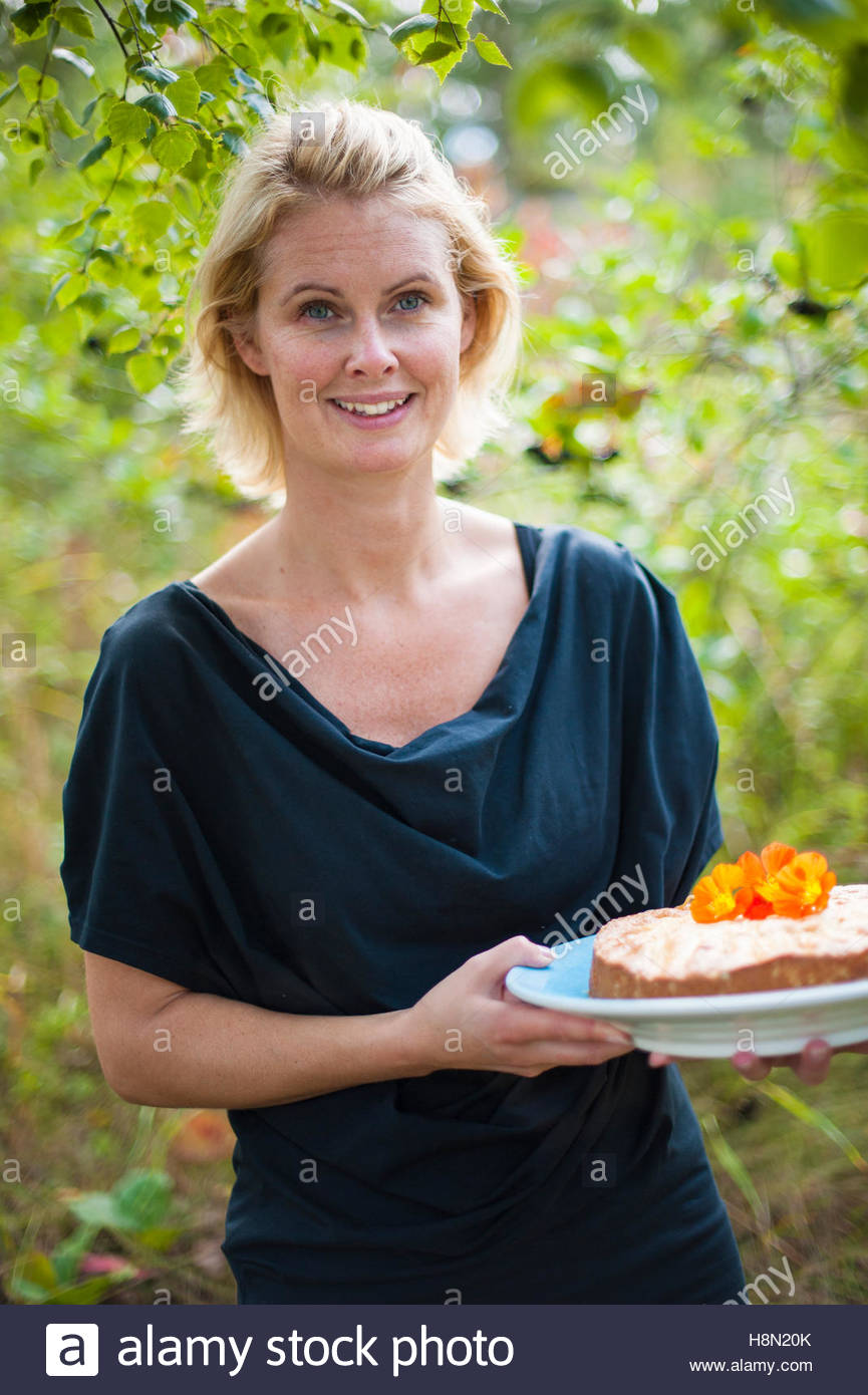 Mid adult woman holding cake - Stock Image