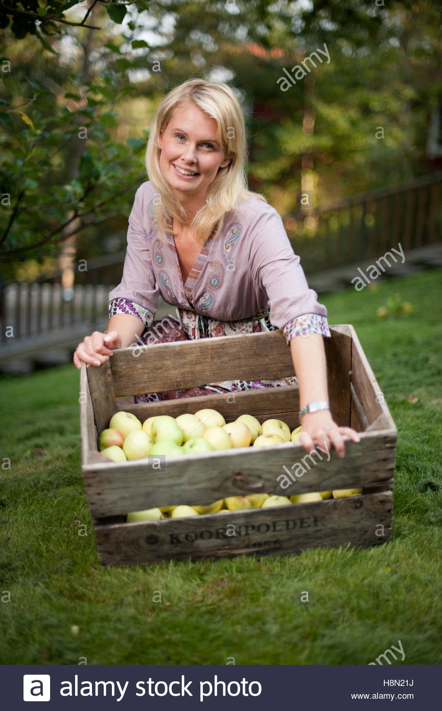 Mid adult woman with crate of apples - Stock Image