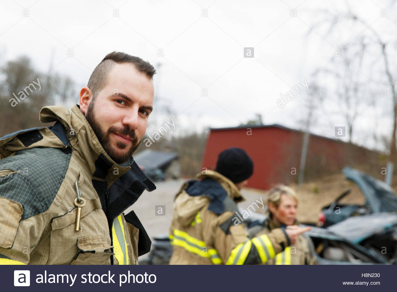 Firefighter looking at camera and others standing beside car - Stock Image