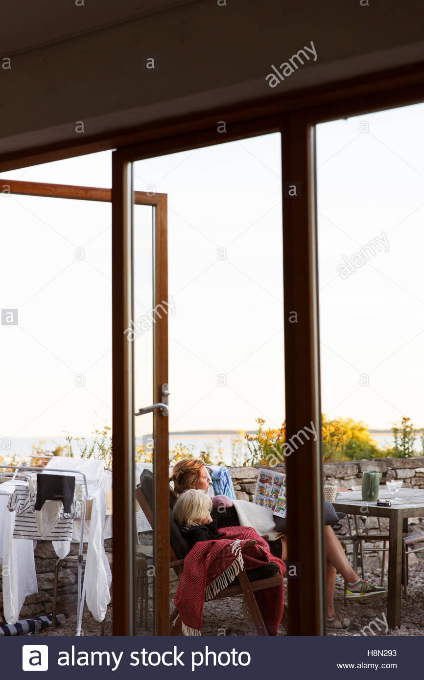 Mother and son (2-3) sitting on patio - Stock Image