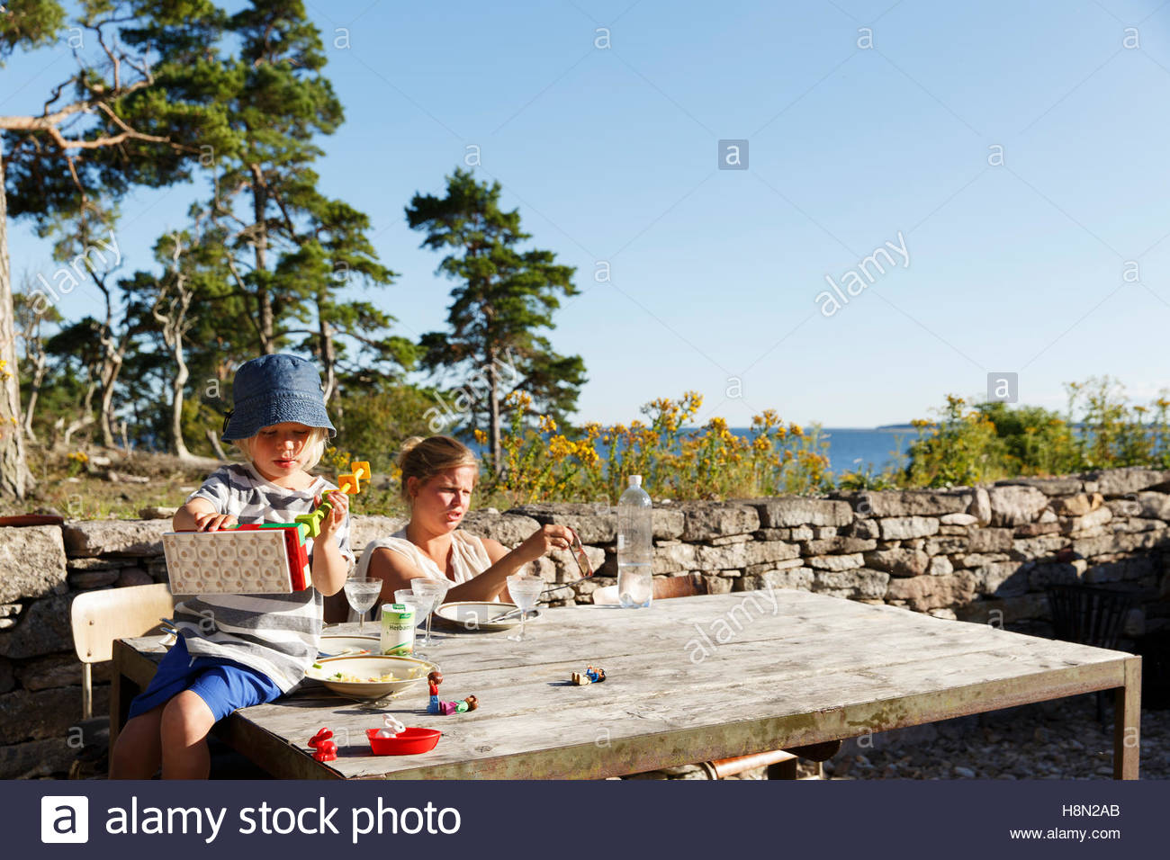 Mother and daughter (2-3) sitting at table outdoors - Stock Image