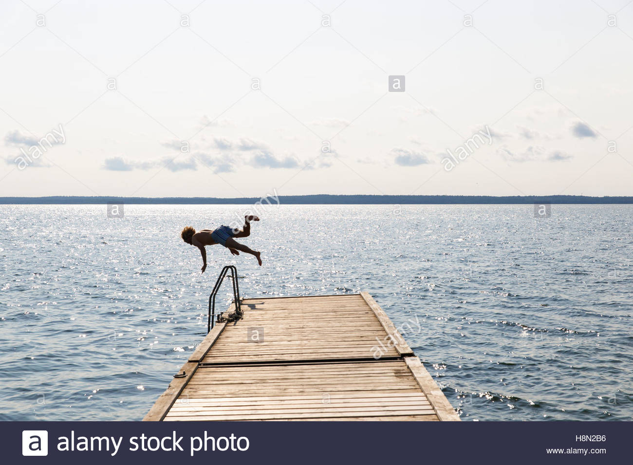 Man jumping off jetty into lake - Stock Image