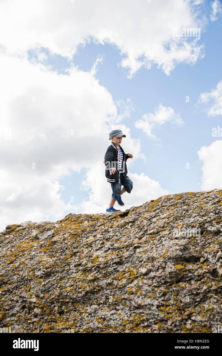 Boy (6-7) walking on top of cliff - Stock Image