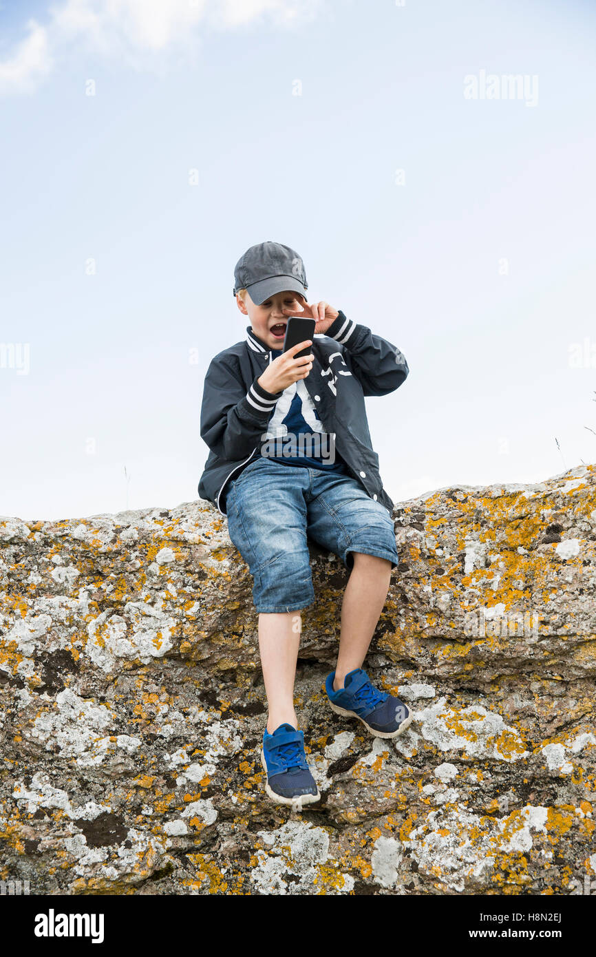 Boy (8-9) sitting at edge of cliff and using telephone - Stock Image
