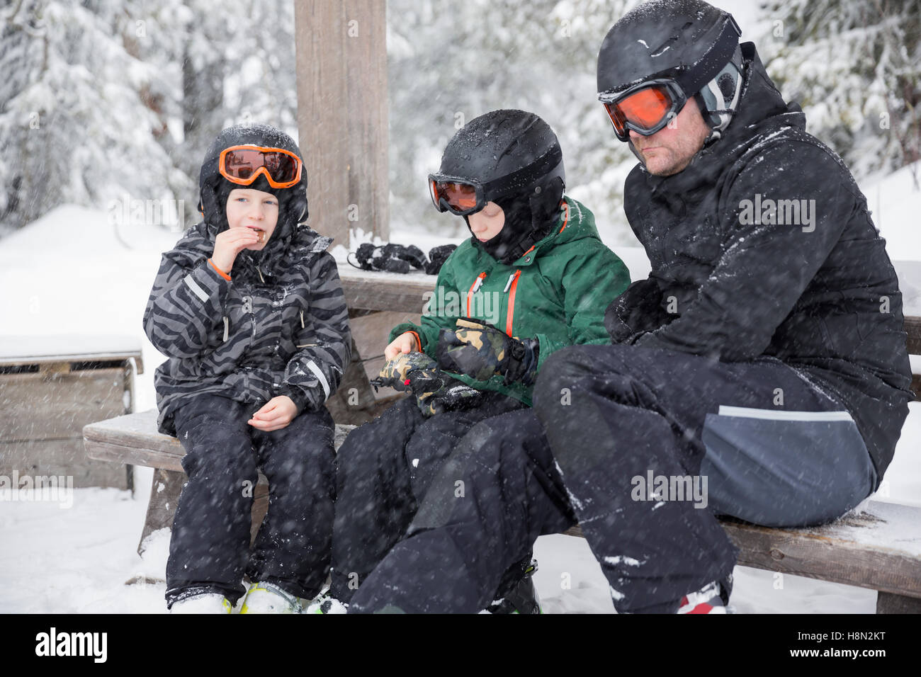 Mature man and boys (6-7, 8-9) wearing helmets and goggles sitting on bench surrounded by winter landscape - Stock Image