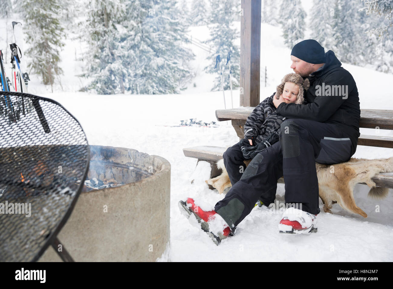 Mature man hugging boy (6-7) sitting on bench by bonfire surrounded by winter landscape - Stock Image