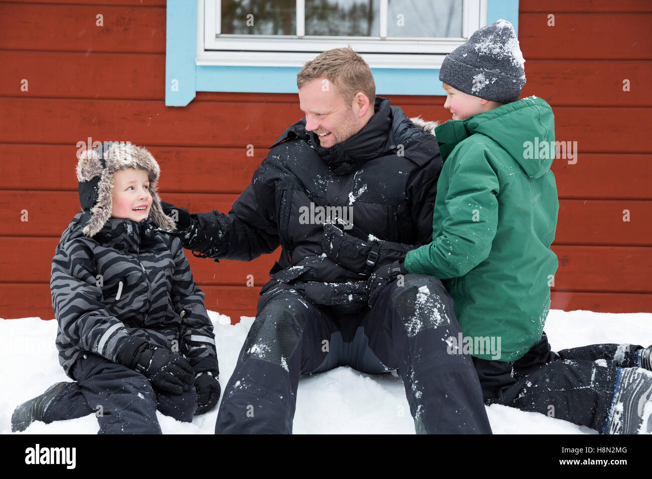 Mature man and boys (6-7, )(8-9) sitting on snow next to wooden cottage wall - Stock Image