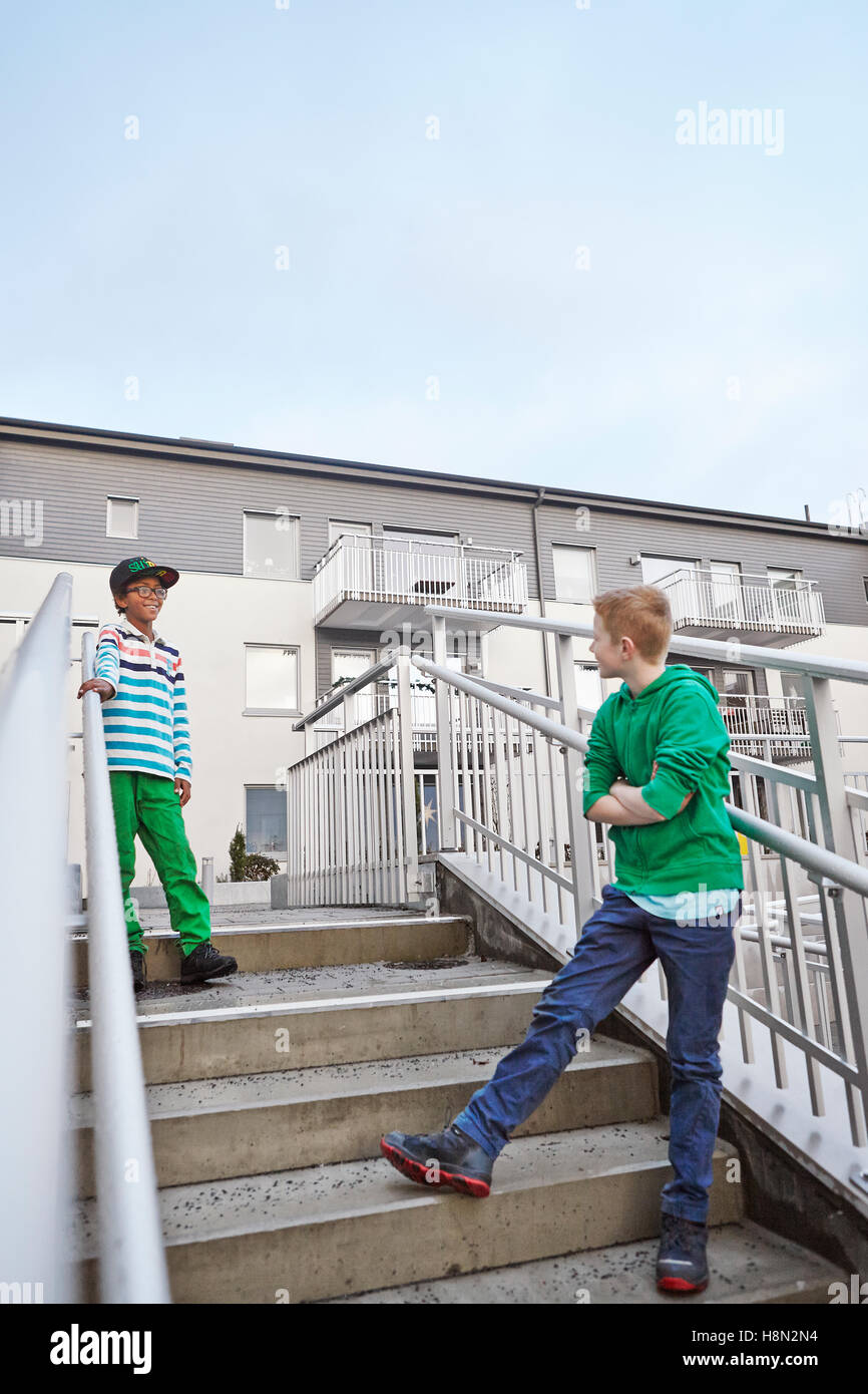 Boys (8-9) standing on stairs and talking - Stock Image